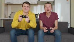 Deux hommes souriant et jouer un jeu vidéo avec enthousiasme clips vidéos