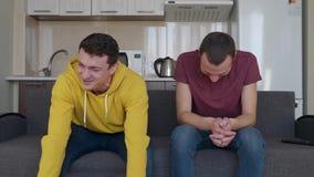Deux hommes sourient Les jeunes types drôles s'asseyent sur le divan et rient très dur à la plaisanterie banque de vidéos