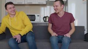 Deux hommes sourient Les jeunes types drôles s'asseyent sur le divan et rient très dur à la plaisanterie clips vidéos