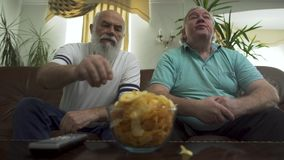 Deux hommes supérieurs beaux s'asseyant sur le sofa en cuir brun regardant la TV Loisirs des retraités banque de vidéos