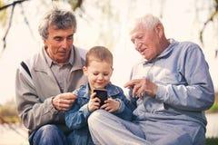 Deux hommes supérieurs et petit-fils à l'aide du téléphone intelligent Photographie stock