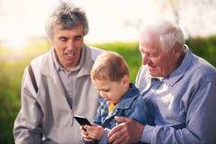 Deux hommes supérieurs et petit-fils à l'aide du téléphone intelligent Images libres de droits