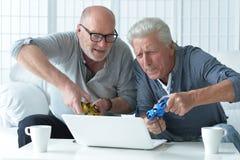 Deux hommes supérieurs jouant sur l'ordinateur portable Image stock