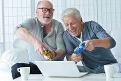 Deux hommes supérieurs jouant sur l'ordinateur portable Images stock