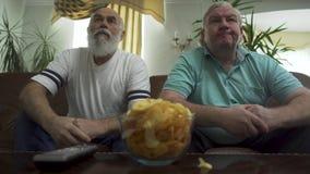 Deux hommes supérieurs mûrs s'asseyant sur le sofa en cuir brun regardant la TV Loisirs des retraités banque de vidéos