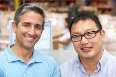 Deux hommes sur le terminal d'ordinateur dans l'entrepôt de distribution photographie stock libre de droits