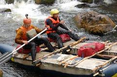 Deux hommes sur un catamaran expédient transportent par radeau sur la rivière du nord Image stock