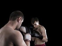 Deux hommes thaïlandais de boxe dans le support de combat sur le fond noir Image stock