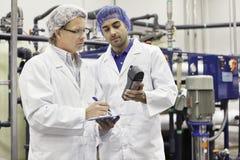 Deux hommes travaillant dans l'usine de mise en bouteilles Images libres de droits