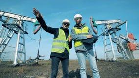 Deux hommes travaillent avec un ordinateur portable sur un gisement de pétrole, fin  banque de vidéos