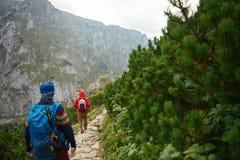 Deux hommes trimardant le long d'une traînée rocheuse dans les montagnes Photographie stock libre de droits