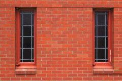 Deux hublots étroits dans le mur de briques Image stock