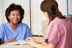 Deux infirmières dans la discussion à la gare d'infirmières Image stock