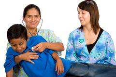 Deux infirmières hispaniques contrôlant le garçon photo stock