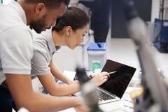 Deux ingénieurs employant le logiciel de programmation de DAO sur l'ordinateur portable photo stock