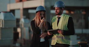 Deux ingénieurs experts analysant le plan de la construction sur le dessus de toit du bâtiment, parlant utilisant une radio banque de vidéos