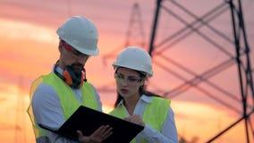 Deux ingénieurs parlent devant les lignes de transmission électriques, travaillant au développement d'énergie renouvelable banque de vidéos