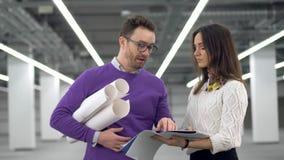 Deux ingénieurs parlent et tiennent des documents, discutant un projet banque de vidéos