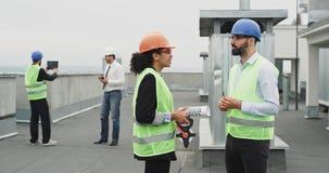 Deux ingénieurs sur le dessus de toit des personnes multi-ethniques de chantier de construction ont une conversation au sujet du  banque de vidéos