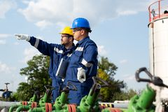 Deux ingénieurs travaillant à l'intérieur de la raffinerie de pétrole et de gaz image stock