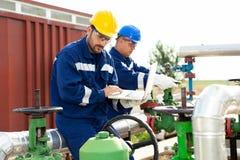 Deux ingénieurs travaillant à l'intérieur de la raffinerie de pétrole et de gaz photographie stock libre de droits