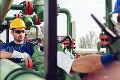 Deux ingénieurs travaillant à l'intérieur de la raffinerie de pétrole et de gaz photos stock