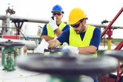 Deux ingénieurs travaillant à l'intérieur de la raffinerie de pétrole et de gaz photo stock