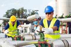 Deux ingénieurs travaillant à l'intérieur de la raffinerie de pétrole et de gaz photographie stock