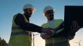 Deux ingénieurs vérifient des turbines de vent, vue inférieure clips vidéos