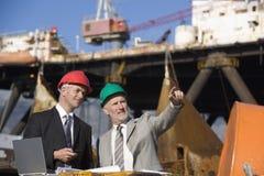 Deux inspecteurs de plateforme pétrolière avec un ordinateur portatif Photo libre de droits