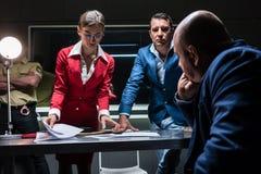 Deux investigateurs persuasifs essayant d'obtenir une confession image stock