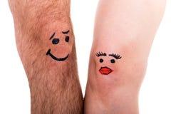 Deux jambes avec des visages, fond blanc Photo stock