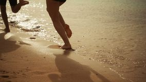 Deux jambes d'enfants fonctionnant à la plage, mouvement lent banque de vidéos