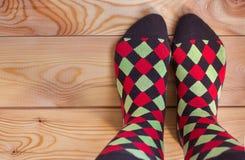 Deux jambes dans les chaussettes multicolores sur un plancher en bois photos libres de droits