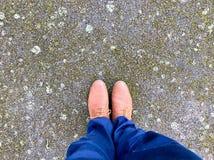 Deux jambes et chaussures se tenant sur un temps battu Photos stock