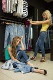 Deux jeans d'achat de filles dans le magasin amie fatiguée Images libres de droits