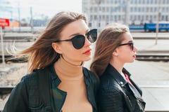 Deux jeune amie attirants se tenant ensemble et posant sur l'appareil-photo Façonnez dehors amies de jeunes de portrait assez mie Image stock