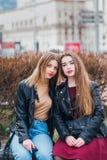 Deux jeune amie s'asseyant ensemble et ayant l'amusement dehors lifestyle Images stock