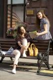 Deux jeune amie s'asseyant sur le banc au centre de ville Photo stock