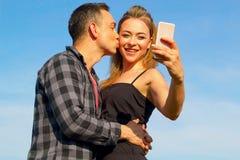 Deux jeune beaux homme et femme faisant le selfie au-dessus du ciel bleu Image stock