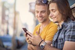 Deux jeune homme, amis intimes comparant des téléphones Images stock