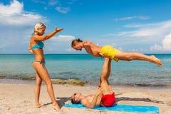 Deux jeune homme et femme sur la plage faisant le yoga de forme physique s'exercent ensemble Élément d'Acroyoga pour la force et  photographie stock libre de droits