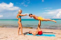 Deux jeune homme et femme sur la plage faisant le yoga de forme physique s'exercent ensemble Élément d'Acroyoga pour la force et  photo libre de droits