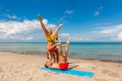 Deux jeune homme et femme sur la plage faisant le yoga de forme physique s'exercent ensemble Élément d'Acroyoga pour la force et  photo stock