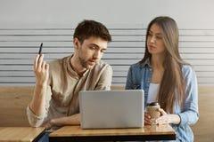 Deux jeunes étudiants dans des vêtements élégants se reposant dans le cafétéria parlant du projet d'étude et regardant le moniteu Photographie stock libre de droits