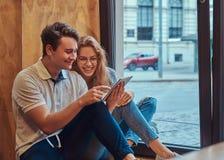 Deux jeunes étudiants heureux à l'aide d'un comprimé numérique tout en se reposant sur un filon-couche de fenêtre à la cantine d' Image stock