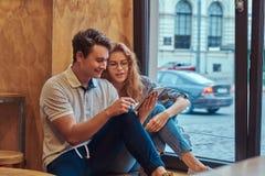 Deux jeunes étudiants heureux à l'aide d'un comprimé numérique tout en se reposant sur un filon-couche de fenêtre à la cantine d' Images stock