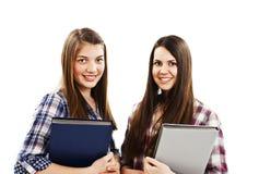 Deux jeunes étudiants retenant un livre et un sourire Image stock