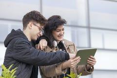 Deux jeunes étudiants, un garçon et une fille, regardant le comprimé et le hav Photos libres de droits