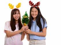 Deux jeunes adolescentes asiatiques heureuses souriant tenant le nouveau YE heureux photo stock
